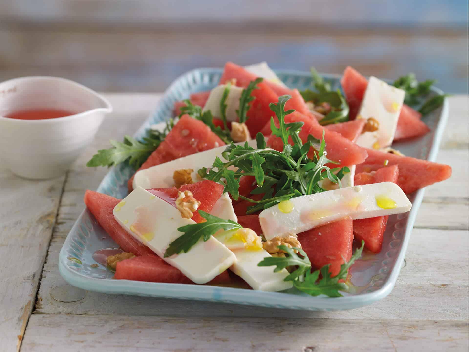 Hirtenkäse angerichtet mit Melonensalat und Rucola