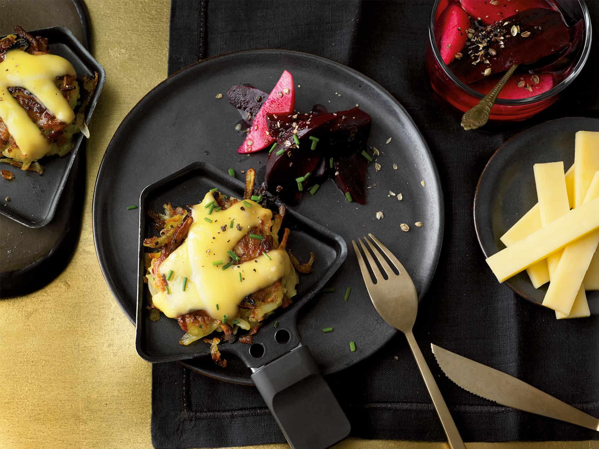 Raclette mit Rösti angerichtet auf roter Beete