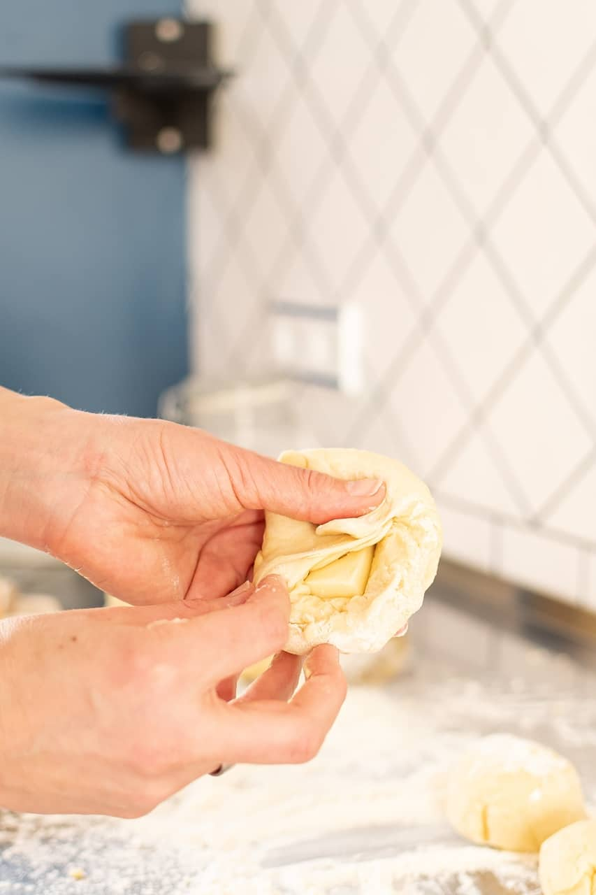 Käse in Teigkugeln drücken