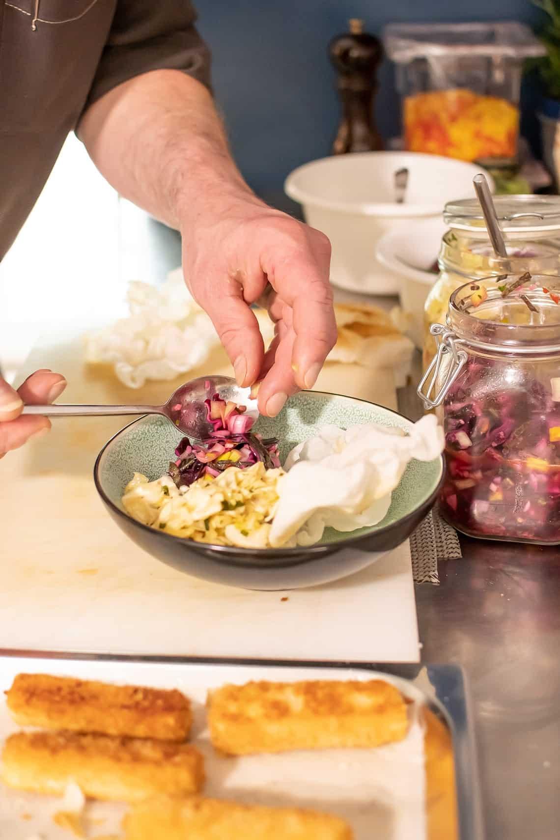 Kimchi und Käsesticks auf Teller legen